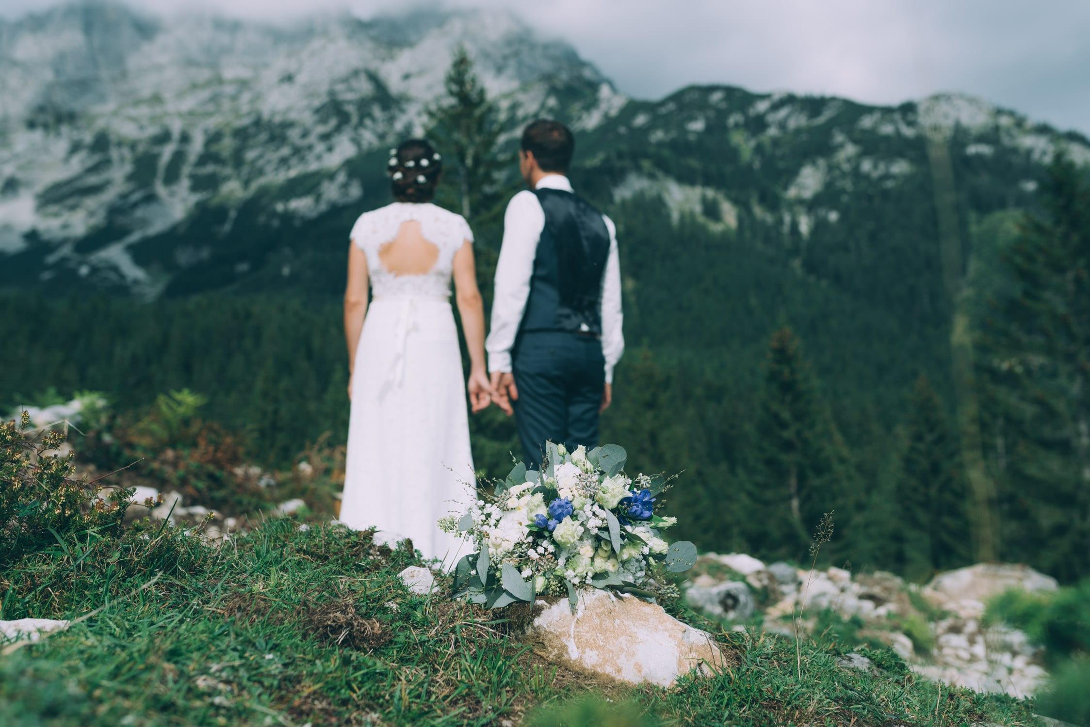 Brautpaar blickt auf die Berge